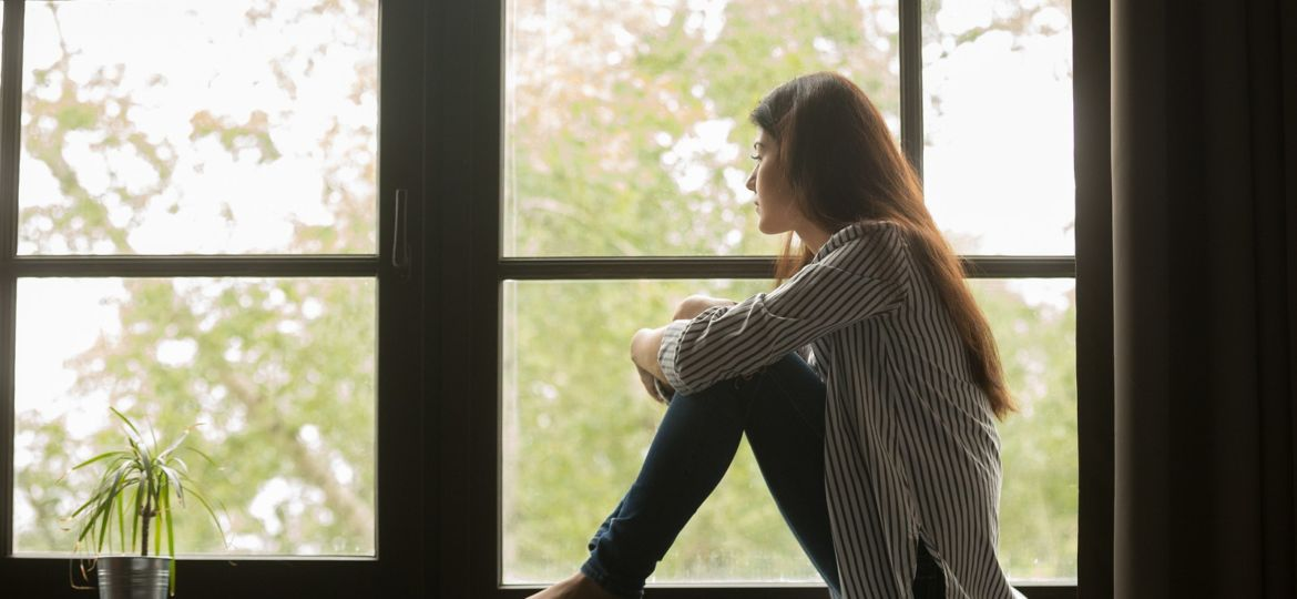 Thoughtful Girl Sitting On Sill Embracing Knees Looking At Windo